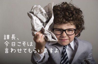 課長、今日こそは言わせてもらいますよという、外国のスーツを着た男の子が新聞をくしゃっと丸める写真画像