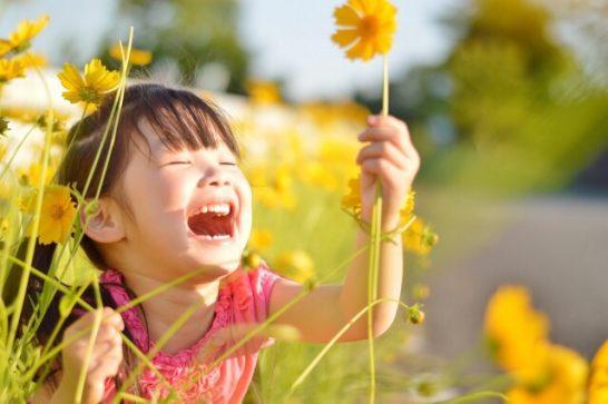 ひまわりを持って大笑いする子供の写真